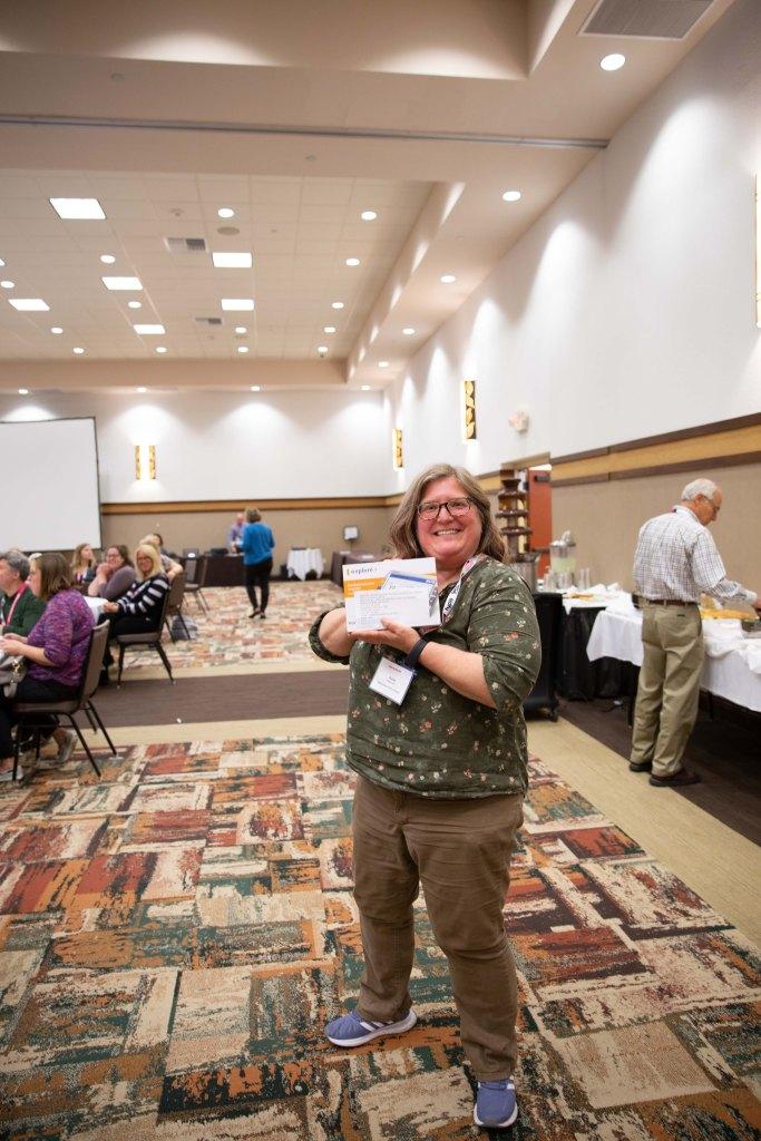 Julie Hapeman holding her raffle prize of a handheld magnifier!